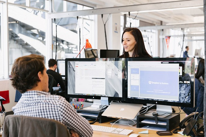Two employees having a conversation as one looks over dual monitors running Dropbox.