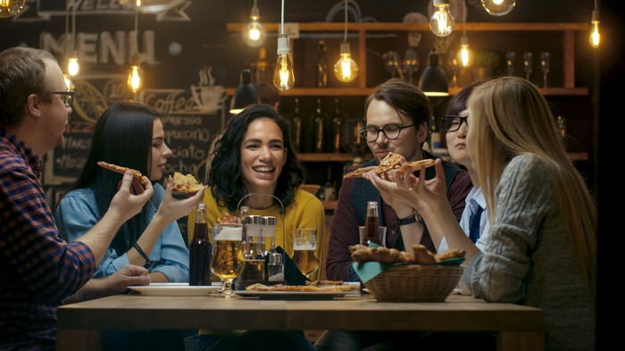 A group of people sitting around a restaurant table eating pizza and drinking beer