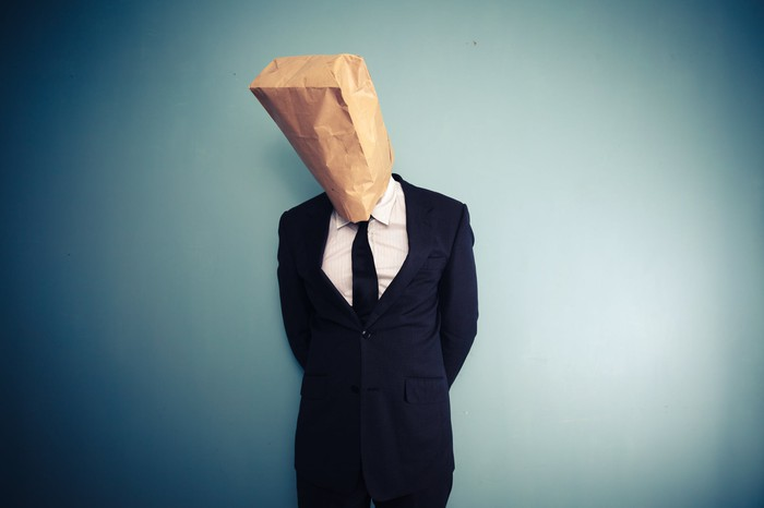 Person in a business suit with a brown paper bag over their head.