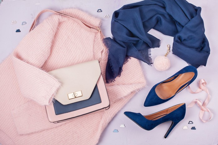 A collection of women's clothing and accessories, including a sweater, scarf, handbag, and high heels