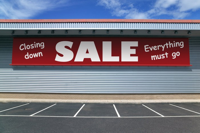 Red banner hanging outside a store, with the words Closing Down, Sales, Everything Must Go.