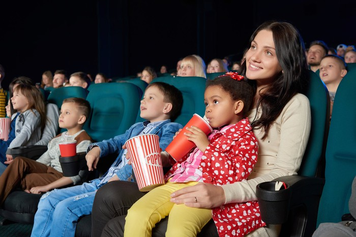 Kids watching a film in a movie theater.