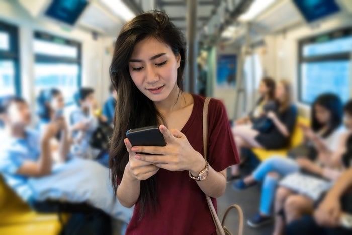 A young woman looks at her smartphone on the subway in an Asian country.
