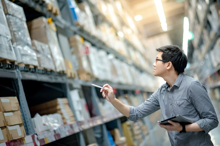 Man counting inventory between shelves in a warehouse