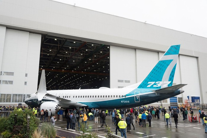 A Boeing 737 MAX next to a hanger surrounded by people.