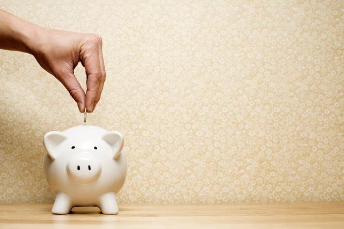 A person dropping a coin into a piggy bank