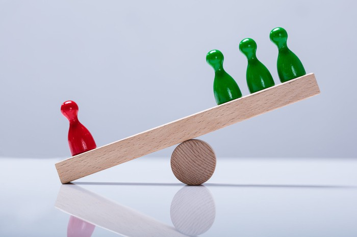 Red and green game pieces on a wooden balance tipped in one direction.