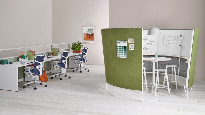 A collaborative office space featuring Herman Miller chairs, desks, and a semi-enclosed creative nook for brainstorming.