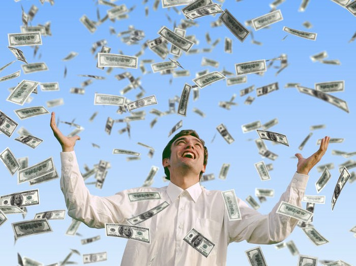 Young man in white long-sleeve shirt looking up and raising arms as many 100-dollar bills fall from the sky.