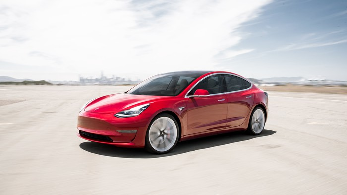 Red Tesla Model 3 parked on a wide, flat area with sun in the background.