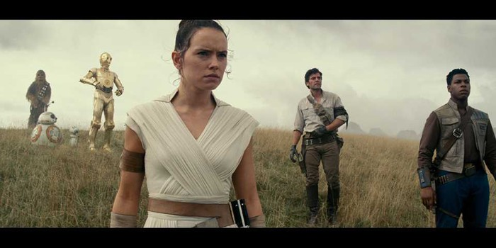 "A number of characters from the latest ""Star Wars"" film stand in a field."