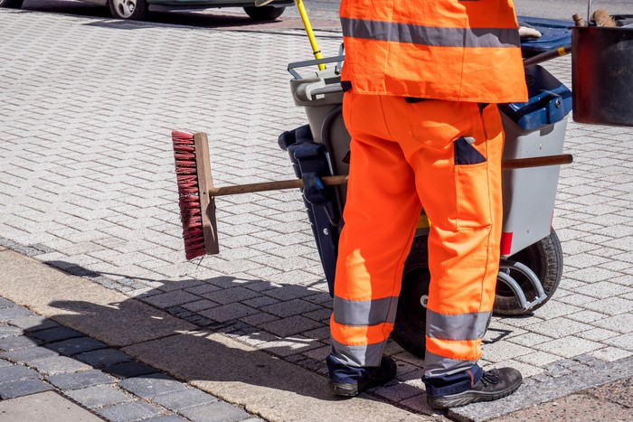 Street sweeper with broom in orange outfit