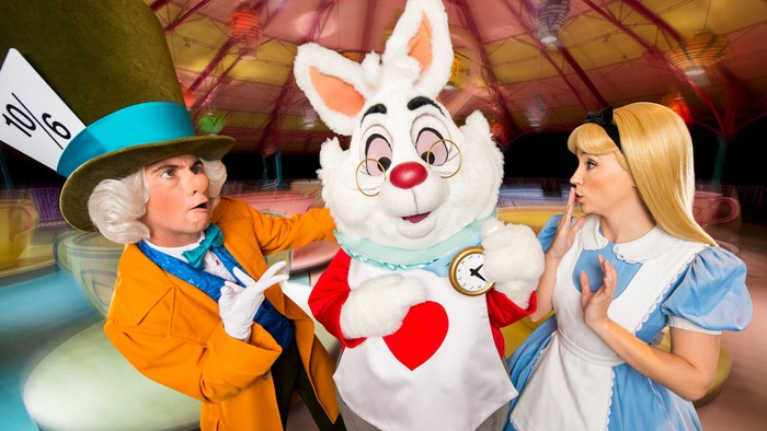 Costumed Alice in Wonderland characters pose in front of the Mad Tea Cups ride at Disney World.