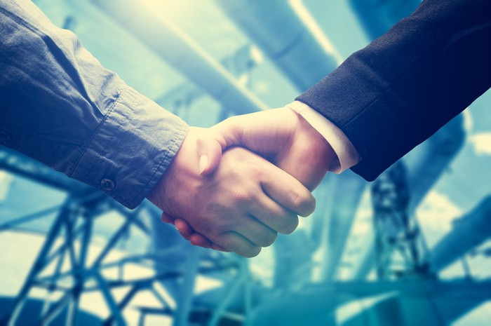 Two people shaking hands in front of pipelines.