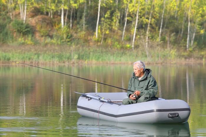 Older man in boat holding fishing rod