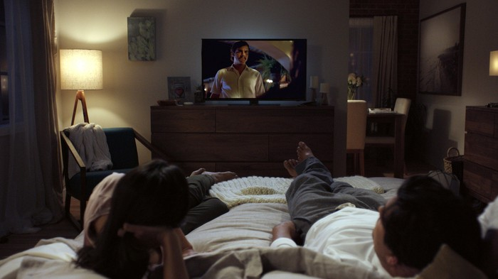 Couple lying in bed watching Netflix show on television.