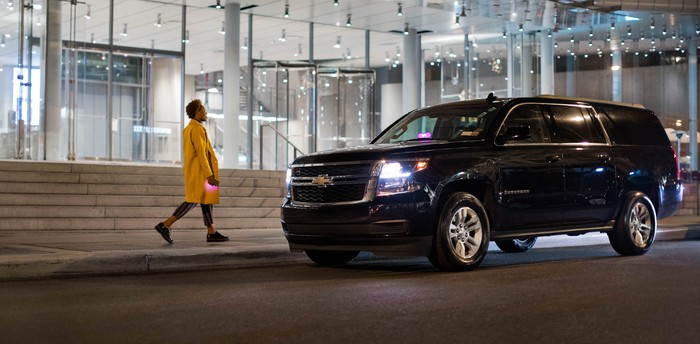 Woman approaching a black Lyft SUV at night