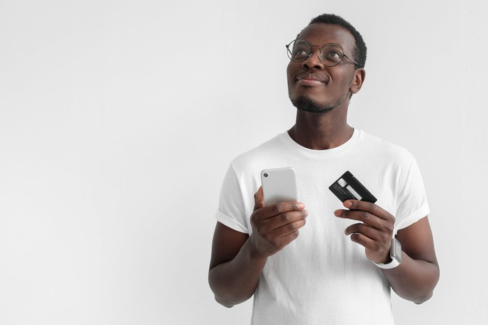 A man holding his smart phone in one hand and a credit card in the other hand