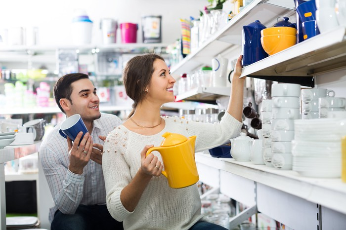 A couple looking at kitchen products in a retail store.