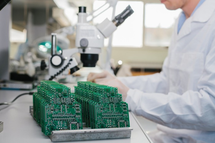 A technician in a white lab coat sits at a microscope, next to a rack full of small circuit boards.