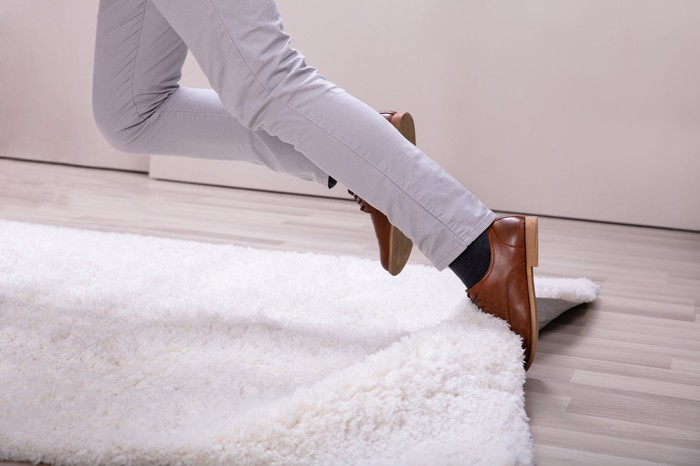 A person tripping on a rug.