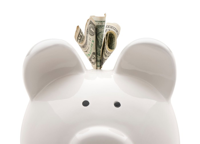 White piggy bank with dollar bill sticking out of it