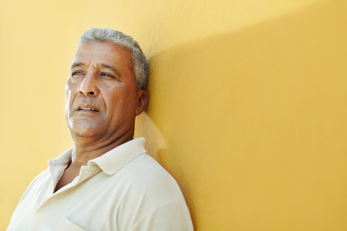 Older man with serious expression leaning against yellow wall