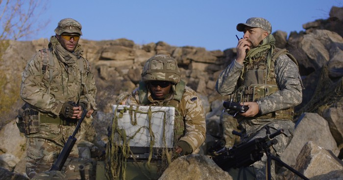 Three soldiers in the field with a laptop and other communications equipment