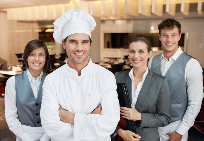 A chef and three waiters, all smiling, standing in a restaurant kitchen