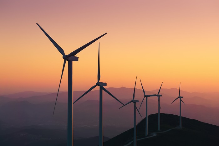 Wind turbines on the top of a hill at dusk.