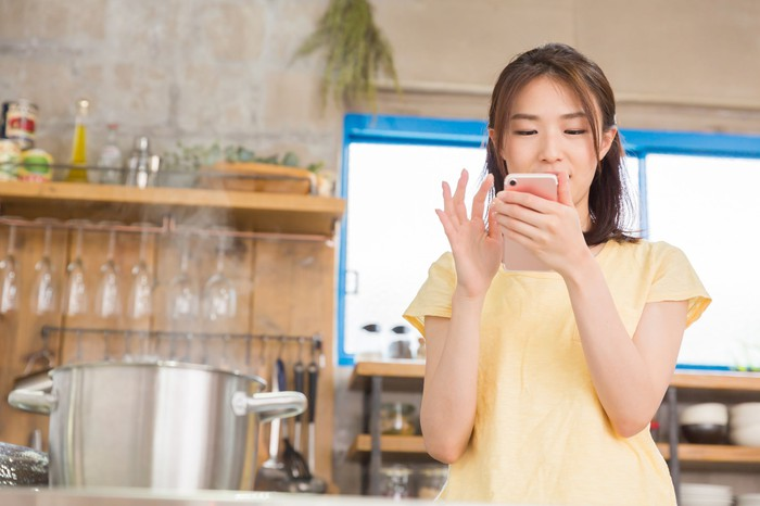 A young woman uses a smartphone in a kitchen.