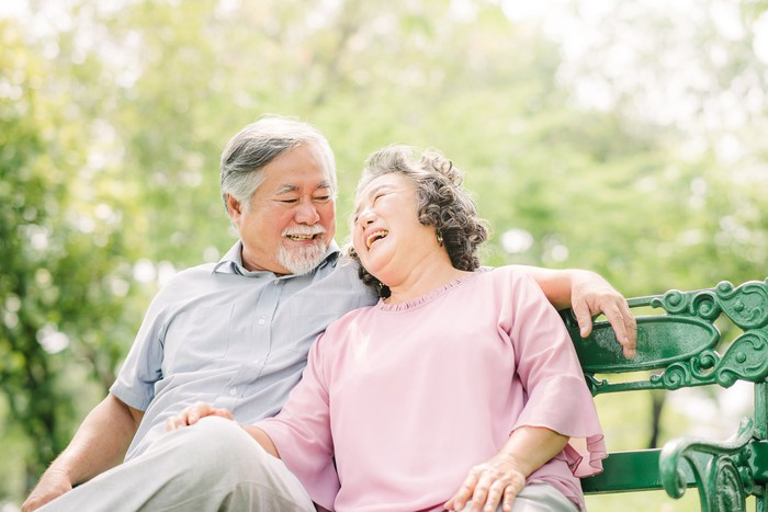 Smiling older couple sitting on a bench.