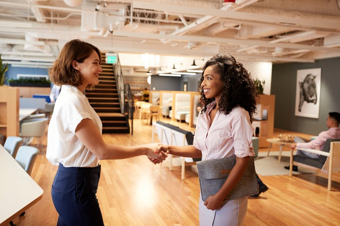 Two professional women shaking hands in a contemporary, relaxed office setting.