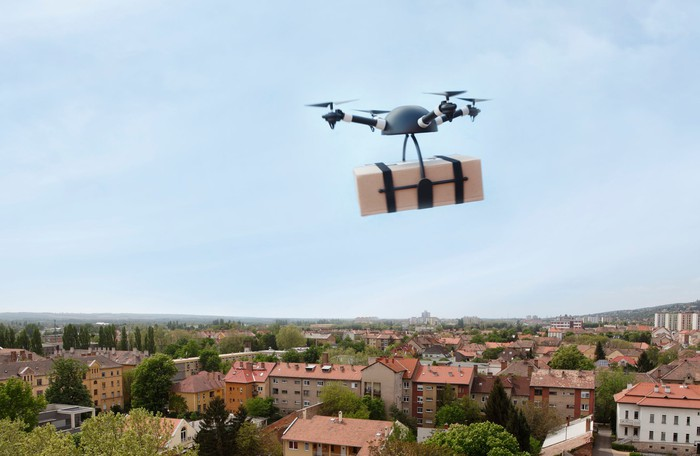 Drone delivering package over city