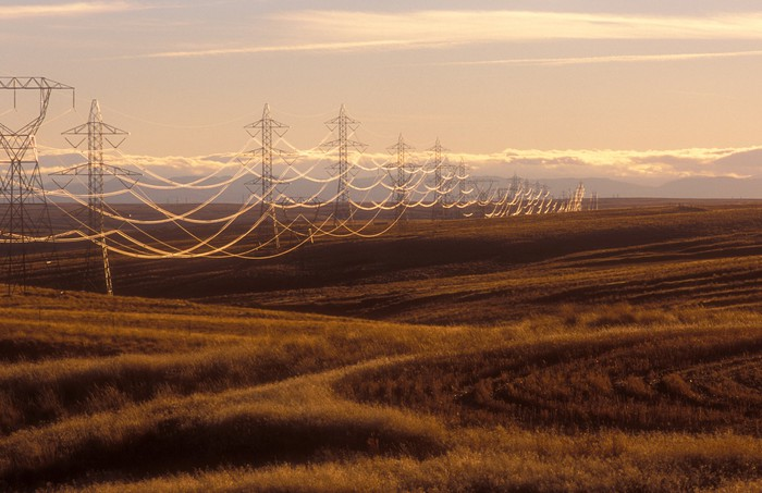 Power transmission lines stretching across a field.