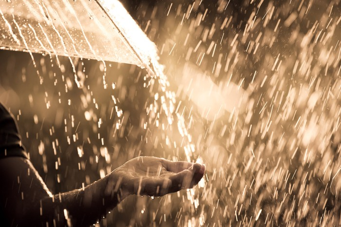 A person holds an umbrella in a heavy rainstorm, reaching the other hand out to catch some water.