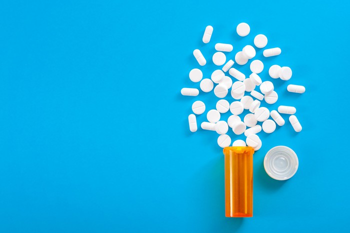 White tablets spilling out of container on blue background