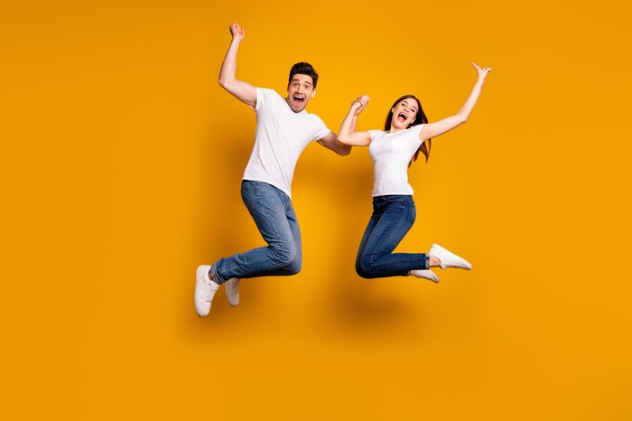 A man and a woman smiling and jumping in the air.