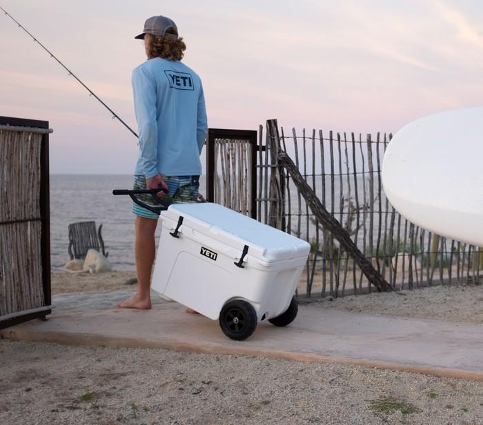 A man carries a Yeti cooler onto the beach wearing a Yeti shirt