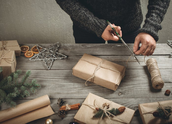 Male hands wrapping Christmas gift on wooden table