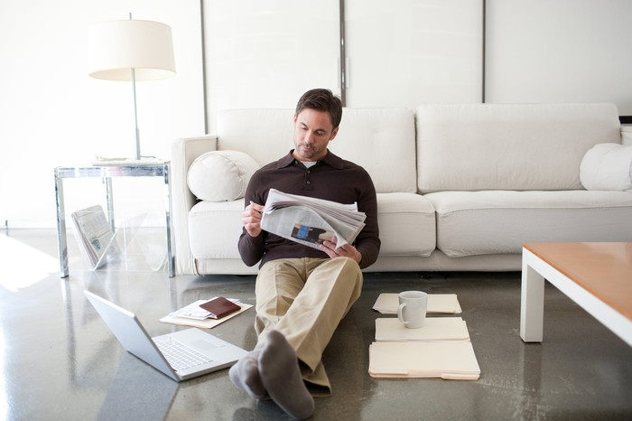 A man casually reading in front of a laptop.