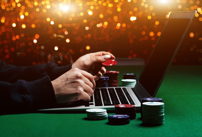 A person using a laptop, surrounded by gambling chips, on a green gambling table.