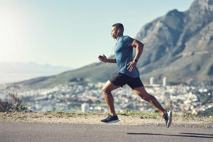 Man running in athletic gear and headphones, with mountains in the background.