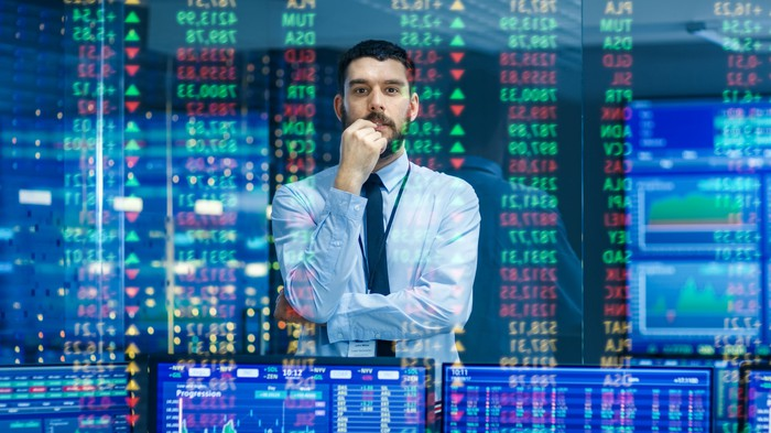 Man watches stock ticker numbers and graphs.