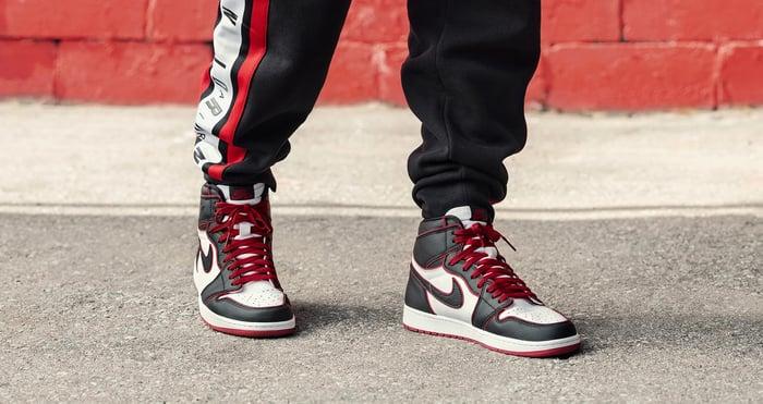 A person wearing Nike Air Jordan 1 High OG shoes.