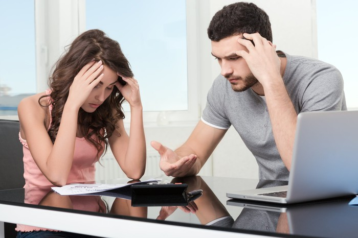 Young man at woman holding their heads; a laptop and documents sit on the table they're at