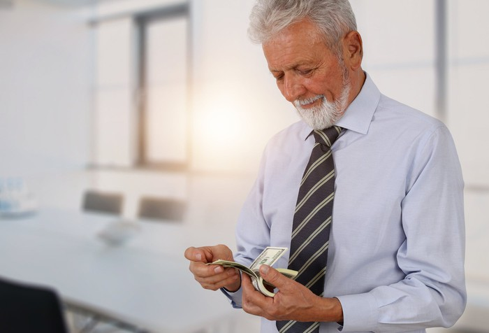 A mature man in a tie counting a stack of cash in his hands.