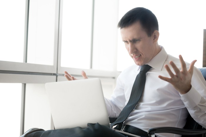 A visibly frustrated businessman holding his hands up while looking at material on his laptop.