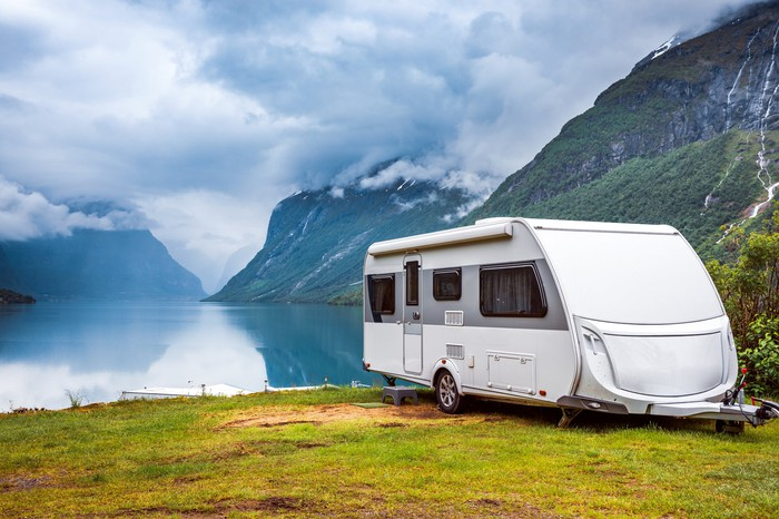 An RV parked near a lake with mountains in the background