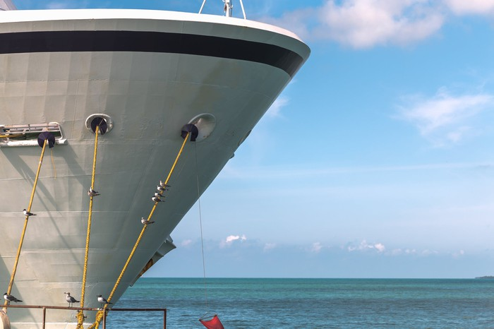 Close-up of the bow of a large cruise ship anchored in a harbor.